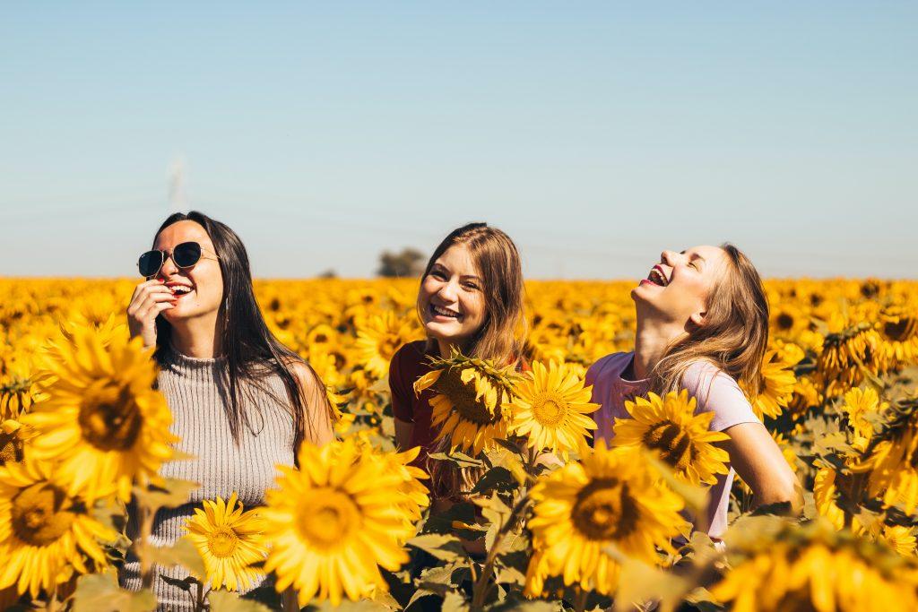 happy girls in field of sunflowers