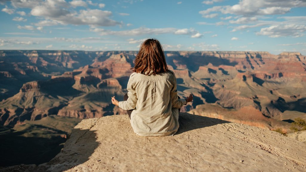 person meditating over grand canyon