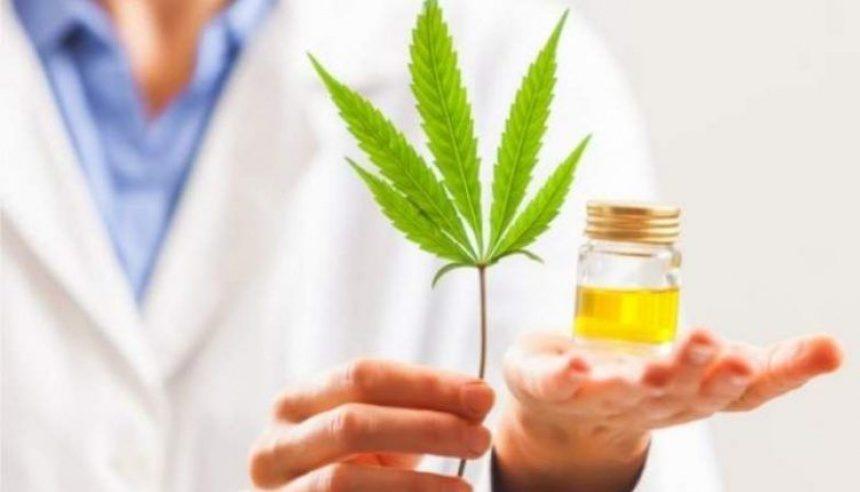 doctor or nurse holding medical marijuana leaf and medical marijuana tincture