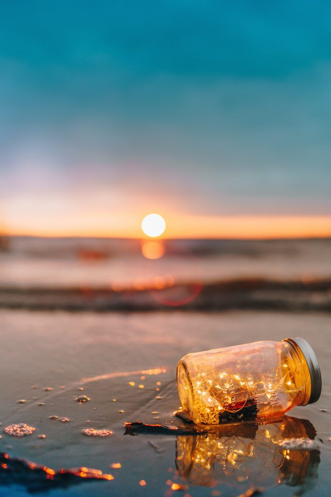 lights in glass jar on beach during sunrise or sunset