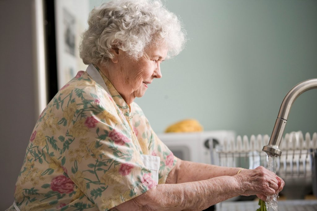 smiling geriatric woman washing her hands