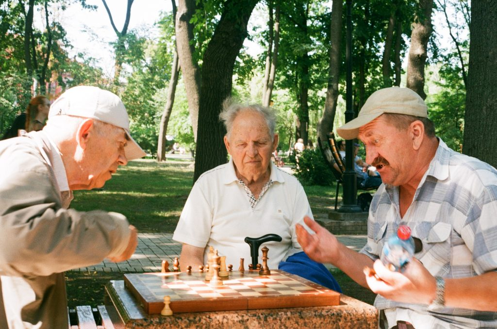 3 geriatric men playing chess in park