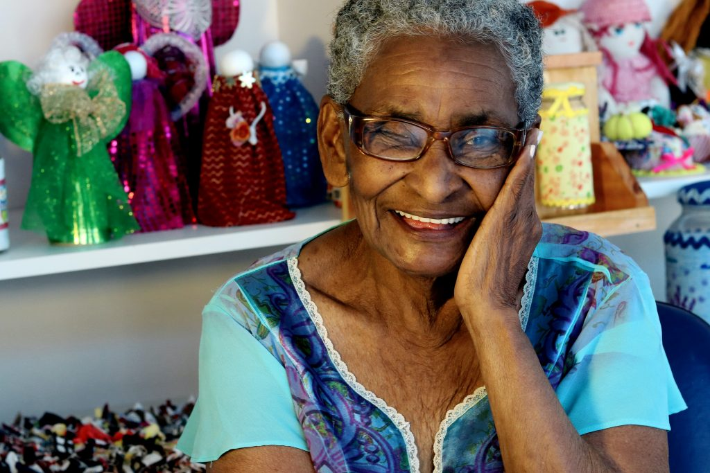 geriatric woman smiling with hand on face
